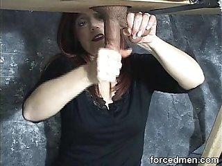 Mistress masturbates man's cock via gloryhole